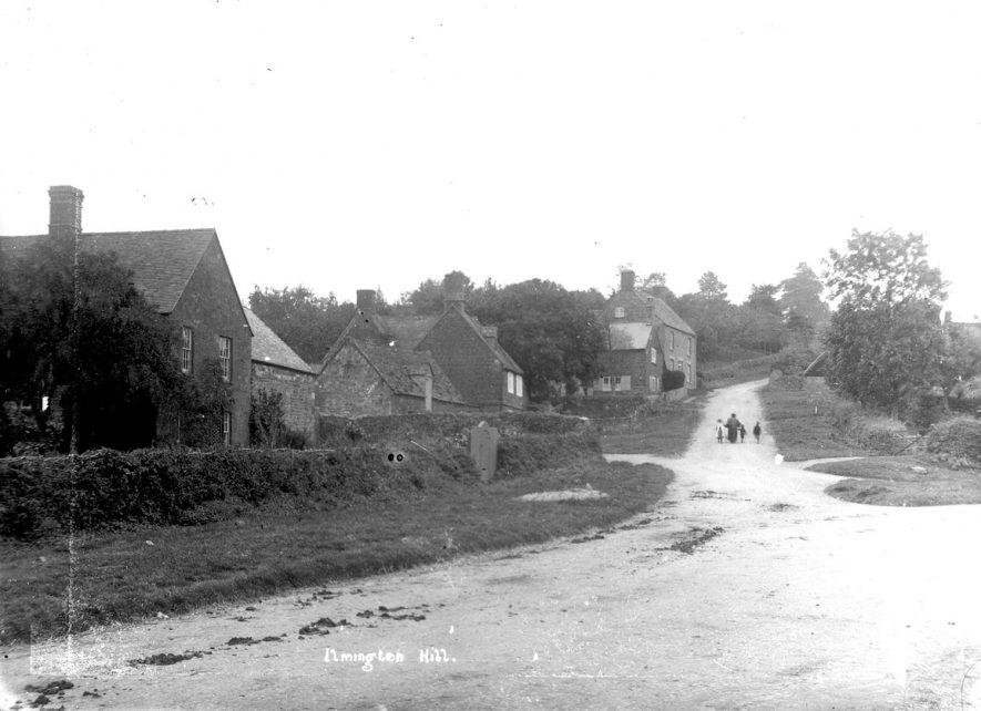 A woman and three children walking up Ilmington Hill, with cottages to the left.  1900s |  IMAGE LOCATION: (Warwickshire County Record Office)