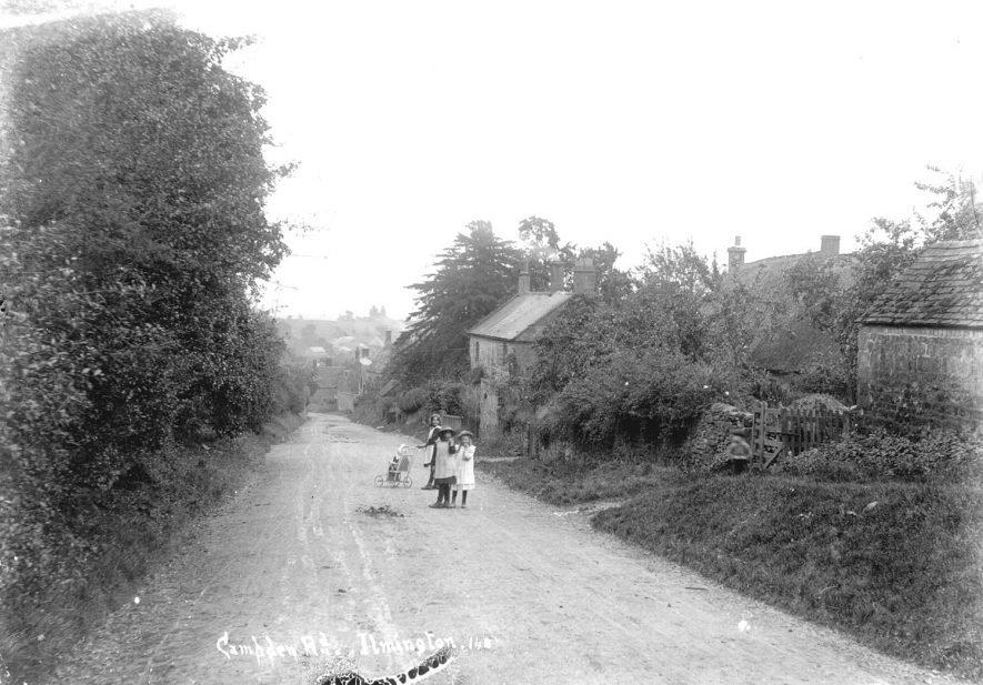 Three girls pushing a child in a pushchair in Campden Road (now Street), Ilmington.  1900s |  IMAGE LOCATION: (Warwickshire County Record Office)