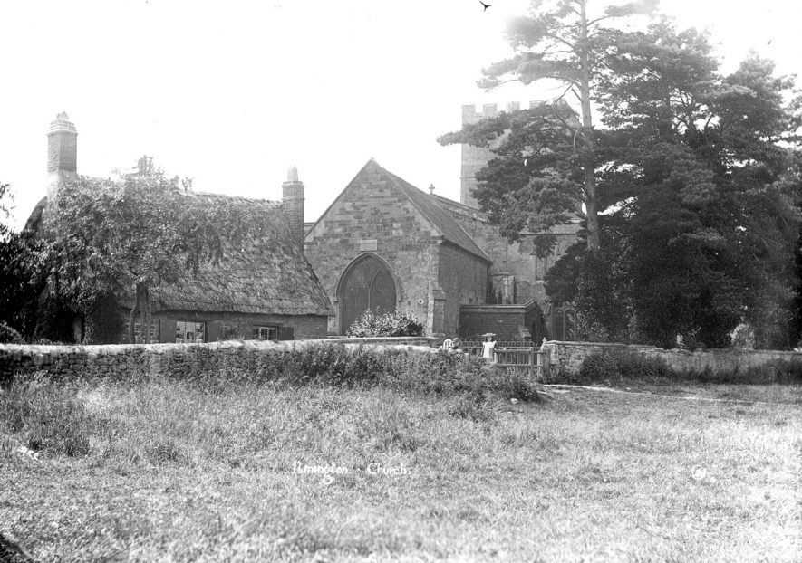 St Mary's church, Ilmington. There is a small thatched cottage to the left and a girl standing at the church gate.  1900s |  IMAGE LOCATION: (Warwickshire County Record Office)