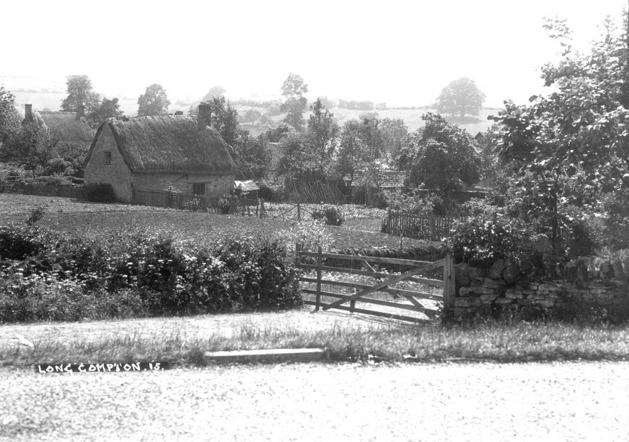 View of two cottages with fields and meadows in the background. Long Compton.  1930s |  IMAGE LOCATION: (Warwickshire County Record Office)