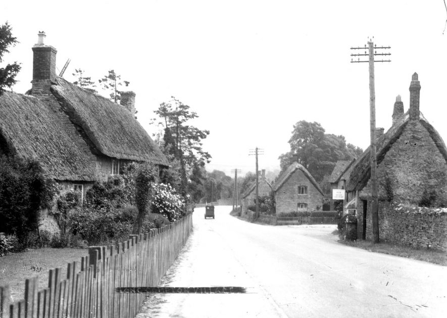 A village street and thatched cottages in Long Compton. The Acorn grocery shop is on the right.  1930s |  IMAGE LOCATION: (Warwickshire County Record Office)