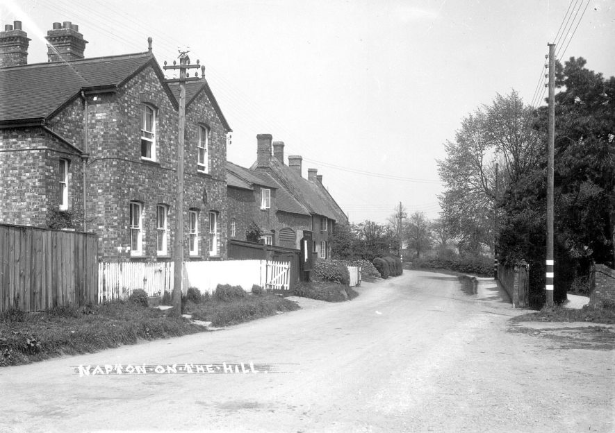 A village street, Napton on the Hill.  1900s.[The second of the semi's with white fencing and gates is the former Police House,the notice board is outside and badge sign can be seen between the two down stair windows.The next cottage was occupied by Len Bradbury and the one next door owned by Tom and Daisy Tarrant. Tom was the village carpenter and coffin maker.] |  IMAGE LOCATION: (Warwickshire County Record Office)