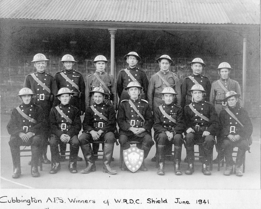 Cubbington Auxiliary Fire Service, winners of the W.R.D.C. Shield in June 1941. The photograph was taken in the school playground.  1941    IMAGE LOCATION: (Warwickshire County Record Office)