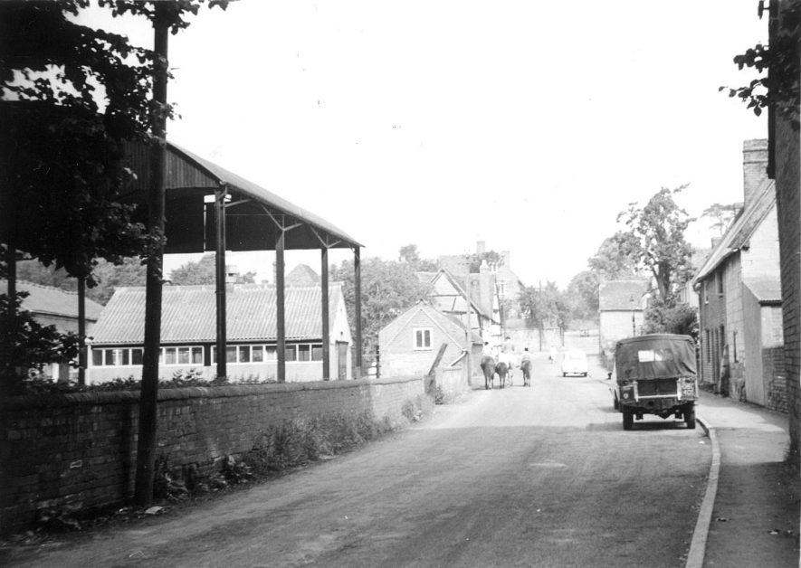 New Street, Cubbington, looking towards Church Lane. A Land Rover is parked on the right and children and ponies are seen in the distance.  1960 |  IMAGE LOCATION: (Warwickshire County Record Office)