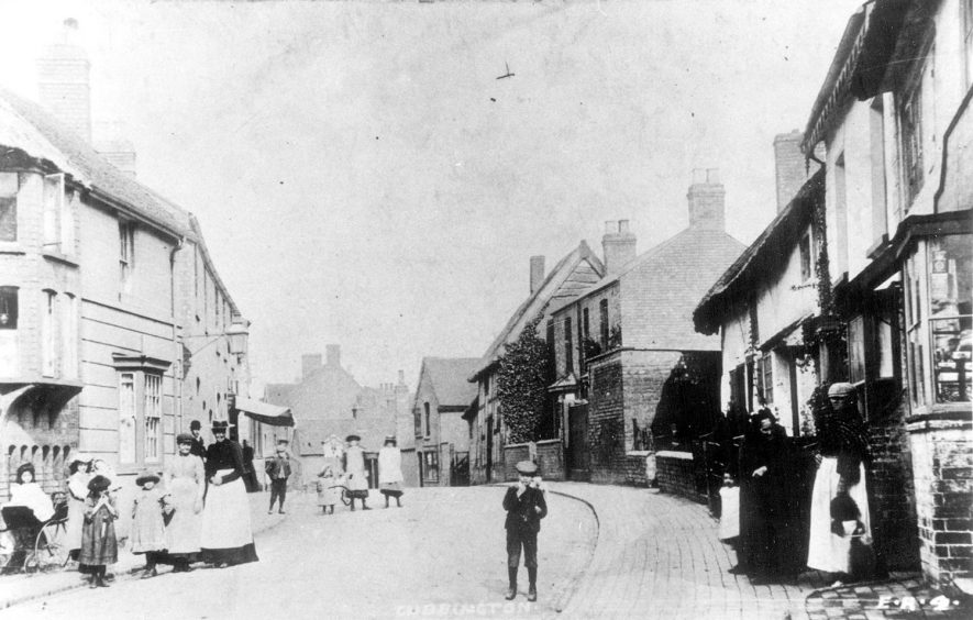 Men, women and children standing in a street in Cubbington. Note the small cart/bath chair on the left.  1900s |  IMAGE LOCATION: (Warwickshire County Record Office)