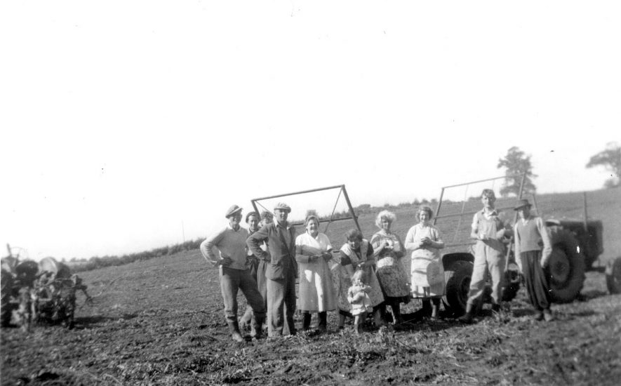 Old Ridge, Cubbington.  Potato picking, a yearly event. Left-right:  Mr Norman Cowley (farmer), Mrs Florence Lee, Joan Kirby, Kathleen Kirby (child), Mrs Nellie Eales, Mary Richardson.  1940s |  IMAGE LOCATION: (Warwickshire County Record Office) PEOPLE IN PHOTO: Richardson, Mary, Richardson as a surname, Lee, Florence, Lee as a surname, Kirby, Kathleen, Kirby, Joan, Kirby as a surname, Eales, Nellie, Eales as a surname, Cowley, Norman, Cowley as a surname