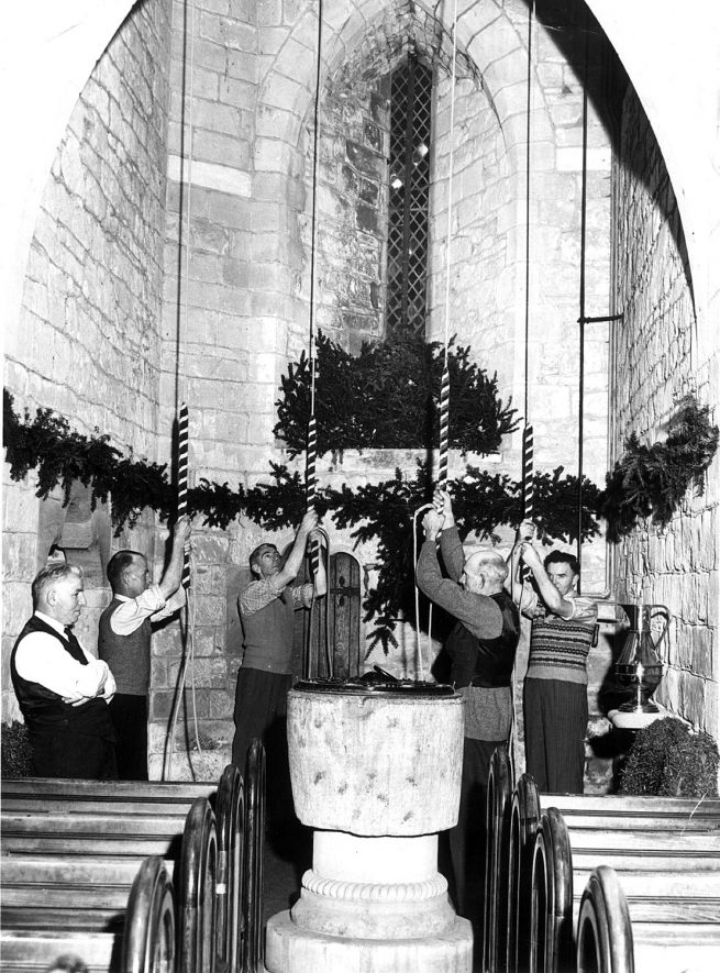 Bell-ringers by the font in Cubbington parish church. Left-right: Spencer Hicks, Arthur Hickman, Alan Rose, Ernie Taylor, Walter Levy.  1950s |  IMAGE LOCATION: (Warwickshire County Record Office) PEOPLE IN PHOTO: Taylor, Ernie, Taylor as a surname, Rose, Alan, Rose as a surname, Levy, Walter, Levy as a surname, Hicks, Spencer, Hicks as a surname, Hickman, Arthur, Hickman as a surname