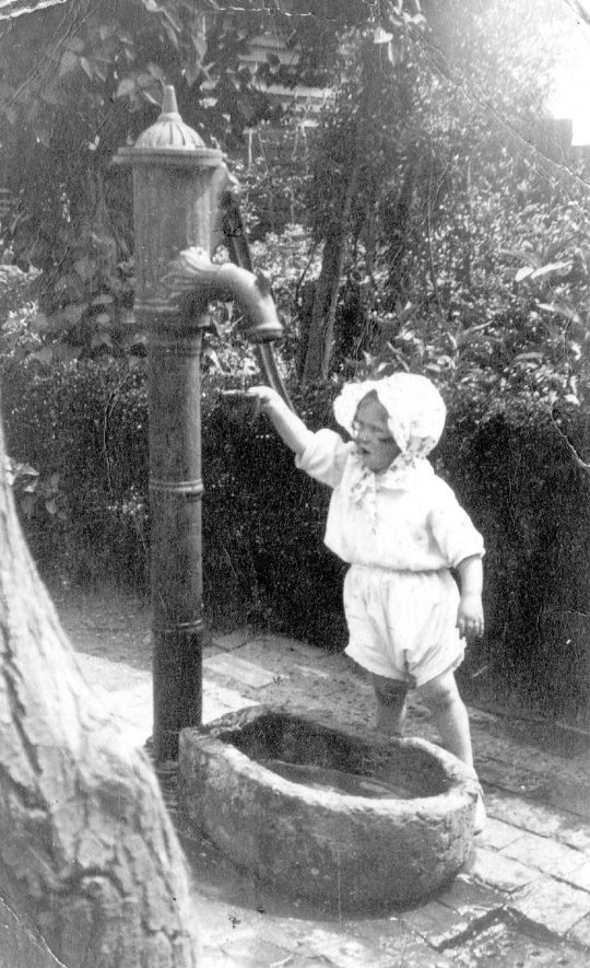 Beryl Rose standing beside a water pump in a garden in High View Road, Cubbington.  1937 |  IMAGE LOCATION: (Warwickshire County Record Office) PEOPLE IN PHOTO: Rose, Beryl, Rose as a surname