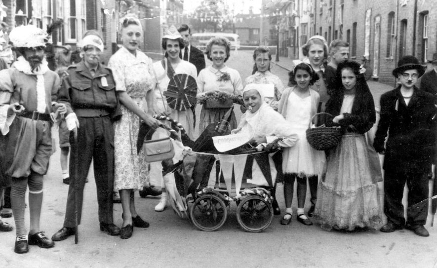 Fancy dress coronation celebrations in Shrubland Street, Leamington Spa.  Left-right. Dave Neale, Tony Walters, John Walters, Brian Bugg, Margaret Bugg.  John French in pram, Graham Bicknell as Charlie Chaplin.  1953 [It has been pointed out that these   celebrations were in St John's Road and fourth from the right with the white hat is Beryl Jean Parker] [It has been further pointed out that this photgraph was taken in Shrubland Street and not St Johns Road. The girl next to the pram in a ballet dress is Linda Bricknell. The girl at the back (?Brittania) is Janet Thompson, the flower girl next to her is Margaret Bastock and the girl between Margaret and Linda is Mavis Usher.] |  IMAGE LOCATION: (Warwickshire County Record Office) PEOPLE IN PHOTO: Walters, Tony, Walters as a surname, Neale, Dave, Neale as a surname, French, John, French as a surname, Bugg, Margaret, Bugg, Brian, Bugg as a surname, Bicknell, Graham, Bicknell as a surname