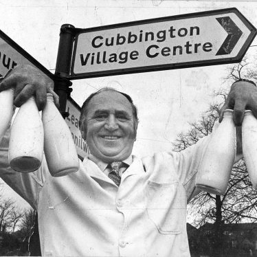 Cubbington.  Milkman under village signpost