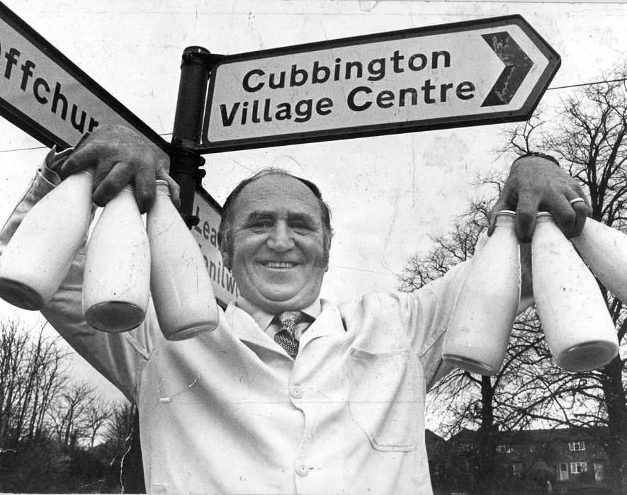 Ted Fairbrother standing holding six milk bottles under sign post showing Cubbington Village Centre.  He and his wife, Mary, took over milk business from his father-in-law in 1949.  They lived at 30, South View Road, New Cubbington.  Fred retired in 1990.  1970s |  IMAGE LOCATION: (Warwickshire County Record Office) PEOPLE IN PHOTO: Fairbrother, Ted, Fairbrother as a surname