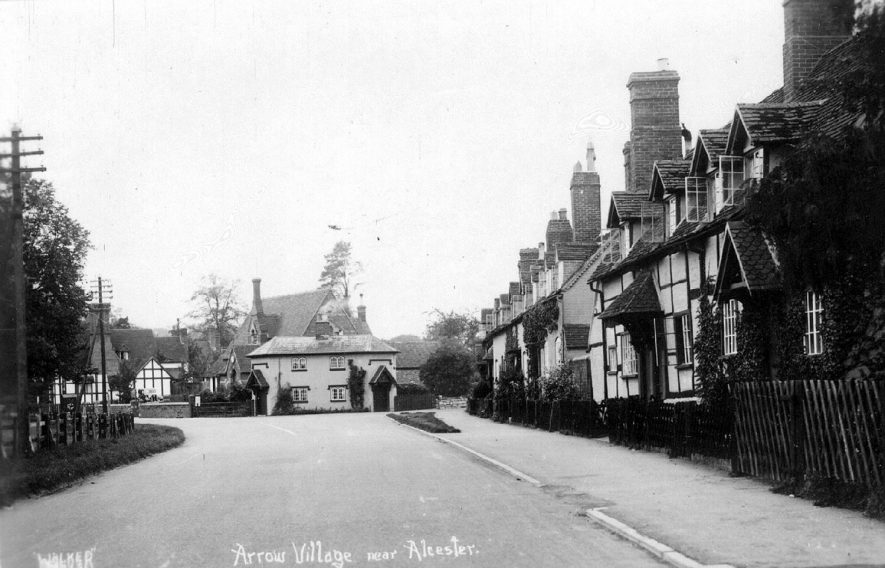Cottages in Arrow. The white building at the end is an unusual tollhouse, in that it has two doors, one facing each road. 1930s |  IMAGE LOCATION: (Warwickshire County Record Office)