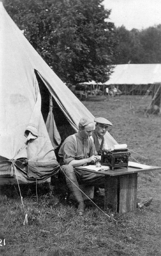 Two men sitting outside a tent with a typewriter on a table before them. Ragley Park.  1915 |  IMAGE LOCATION: (Warwickshire County Record Office)