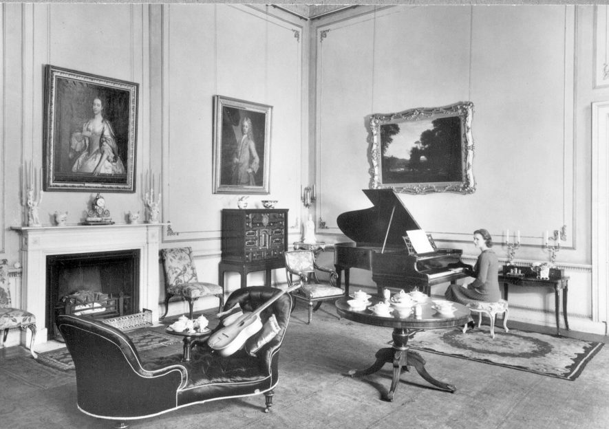 The Marchioness of Hertford seated at a piano in one of the rooms at Ragley Hall.  1950s |  IMAGE LOCATION: (Warwickshire County Record Office) PEOPLE IN PHOTO: Hertford, The Marchioness of