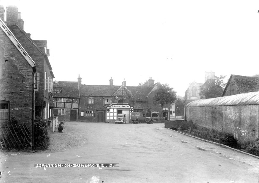 A village street in Stretton on Dunsmore with the Electric Bakery and All Saint's church in the background.  1930s |  IMAGE LOCATION: (Warwickshire County Record Office)