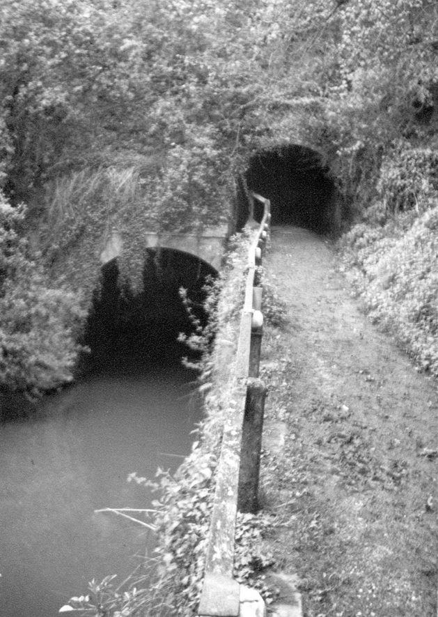 The north entrance to Shrewley canal tunnel which is 433yards long. On the right is the tow-path leading to a way over Shrewley Common Road.  1950s |  IMAGE LOCATION: (Warwickshire County Record Office)