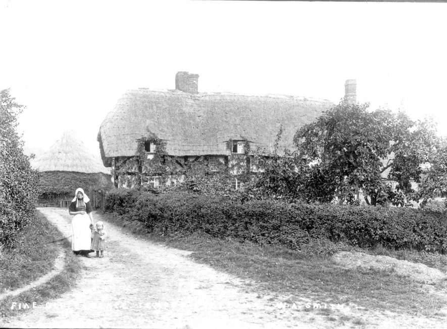 Old thatched and timbered cottage with a lady and child standing in driveway. Temple Grafton.  1900s |  IMAGE LOCATION: (Warwickshire County Record Office)