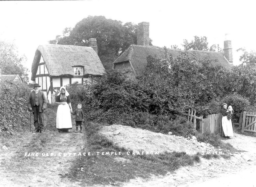 Old thatched and timbered cottages in Temple Grafton. A man, woman and child are standing in the driveway of one cottage and a woman and baby are standing at the gate of another cottage.  1900s |  IMAGE LOCATION: (Warwickshire County Record Office)