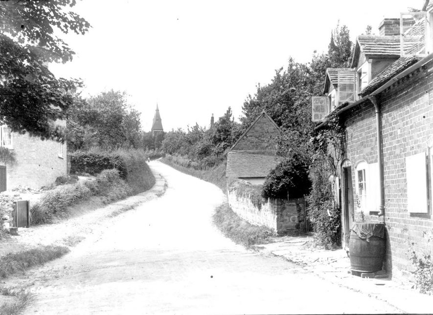 Village lane in Temple Grafton. The church is seen in the background.  1900s |  IMAGE LOCATION: (Warwickshire County Record Office)