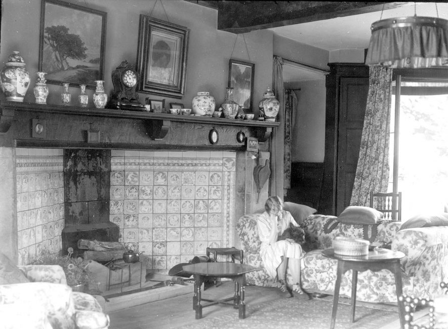 Interior of one of the rooms at Alveston Manor showing a lady seated on a sofa with a dog.  1920s |  IMAGE LOCATION: (Warwickshire County Record Office)