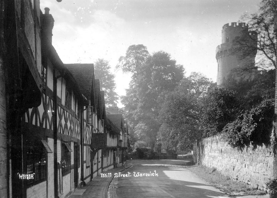 Old timbered houses in Mill Street, Warwick,  with a view of Caesar's Tower.  1930s |  IMAGE LOCATION: (Warwickshire County Record Office)