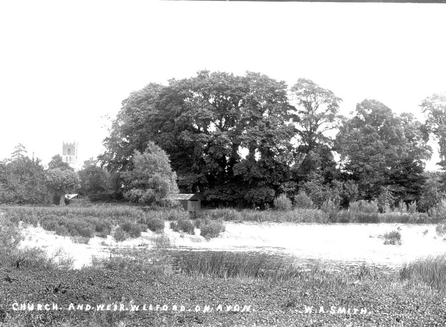 The weir on the River Avon with the church tower in the background at Welford on Avon.  1900s |  IMAGE LOCATION: (Warwickshire County Record Office)