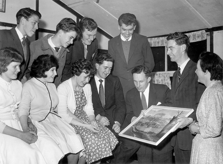 Group of young men and women looking at a landscape picture. Back row, left to right - not known, Chris Rose, Roy Rogers, David Boswell. Front row - Margaret Jones, Pat Hawker, Gail Houghton, Derek Smith, Mr Houghton, John Harrison, Mrs Harrison.  1960s |  IMAGE LOCATION: (Warwickshire County Record Office) PEOPLE IN PHOTO: Smith, Derek, Smith as a surname, Rose, Chris, Rose as a surname, Rogers, Roy, Rogers as a surname, Jones, Margaret, Jones as a surname, Houghton, Mr, Houghton, Gail, Houghton as a surname, Hawker, Pat, Hawker as a surname, Harrison, Mrs, Harrison, John, Harrison as a surname, Boswell, David, Boswell as a surname