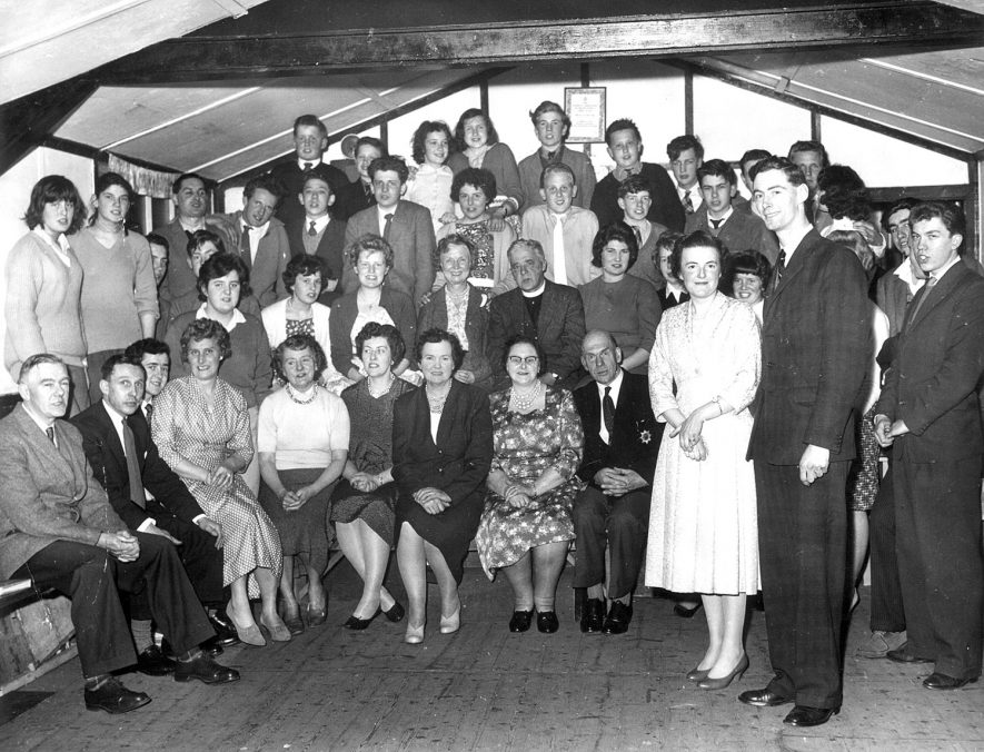 Large group of men and women in a hall. Back row, left to right - Alun Jones, Roy Gatfield, Helen Corral, Janet Barnes, Ray Hawker, not known, not known, Peter Davies. Second row - not known, not known, Ivor Smith, not known, not known, David Wood, Jane Osbourne, William Marshall, Royce Davies, Chris Rose. Third row - John Carrol, Brian Barnes, Ann Cowlishow, Gail Houghton, Lynsey Parry, Mrs Hulme, Cannon Ecclestone, Sheila Hawker, Elizabeth Jones, Margaret Jones, Tony Barnes, David Boswell. Front row - Bernard Rose, Mr Houghton, Derek Smith, Mrs Houghton, Mrs Ecclestone, Mrs Mowforth, Mrs Midgley, Mrs Hind, Mr Hind. Standing at the front - Mrs Harrison, John Harrison. Offchurch.  1960s |  IMAGE LOCATION: (Warwickshire County Record Office) PEOPLE IN PHOTO: Wood, David, Wood as a surname, Smith, Ivor, Smith, Derek, Rose, Chris, Rose, Bernard, Parry, Lynsey, Osbourne, Jane, Mowforth, Mrs, Midgley, Mrs, Marshall, William, Jones, Margaret, Jones, Elizabeth, Jones, Alun, Jones as a surname, Hulme, Mrs, Hulme as a surname, Houghton, Mrs, Houghton, Gail, Houghton as a surname, Hind, Mrs, Hind, Mr, Hind as a surname, Hawker, Sheila, Hawker, Ray, Hawker as a surname, Harrison, Mrs, Harrison, John, Harrison as a surname, Gatfield, Roy, Gatfield as a surname, Ecclestone, Mrs, Ecclestone, Cannon, Ecclestone as a surname, Davies, Royce, Davies, Peter, Davies as a surname, Cowlishaw, Ann, Cowlishaw as a surname, Corral, Helen, Corral as a surname, Carrol, John, Carrol as a surname, Boswell, David, Boswell as a surname, Barnes, Tony, Barnes, Janet, Barnes, Brian, Barnes as a surname