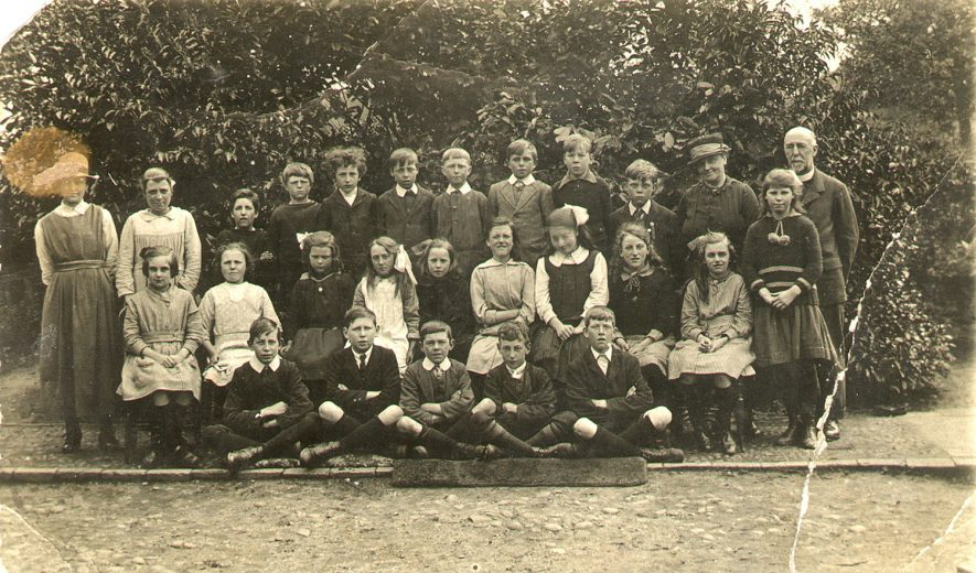 School group photograph. Back row, left to right - Mrs Davies, Norah Barnett, Jim Hirons, Harry Bowles, Sid Berry, Bill Singleton, Fred Fisher, Cyril Isham, Tom Marshall, Bill Hastings, Head Teacher Mrs Smith and the Vicar, Rev. J. Ashe. Second row - Olive Hewitt, Anne Bowles, Dorothy Hitchman, Eva Claridge, Florrie Isham, Frances Ayres, Dorothy Berry, Ella Hewitt, Mary Bowles. Front row - Ted Clinton, Eric Boyles, Bernard Rose, Alfred Berry, Reg French. Offchurch.  1918 |  IMAGE LOCATION: (Warwickshire County Record Office) PEOPLE IN PHOTO: Smith, Mrs, Smith as a surname, Singleton, Bill, Singleton as a surname, Rose, Bernard, Rose as a surname, Marshall, Tom, Marshall as a surname, Isham, Florrie, Isham, Cyril, Hitchman, Dorothy, Hitchman as a surname, Hirons, Jim, Hirons as a surname, Hewitt, Olive, Hewitt, Ella, Hewitt as a surname, Hastings, Bill, Hastings as a surname, French, Reg, French as a surname, Fisher, Fred, Fisher as a surname, Davies, Mrs, Davies as a surname, Clinton, Ted, Clinton as a surname, Claridge, Eva, Claridge as a surname, Boyles, Eric, Boyles as a surname, Bowles, Mary, Bowles, Harry, Bowles, Anne, Bowles as a surname, Berry, Sid, Berry, Dorothy, Berry, Alfred, Berry as a surname, Barnett, Norah, Barnett as a surname, Ayres, Frances, Ayres as a surname, Ashe, Revd J