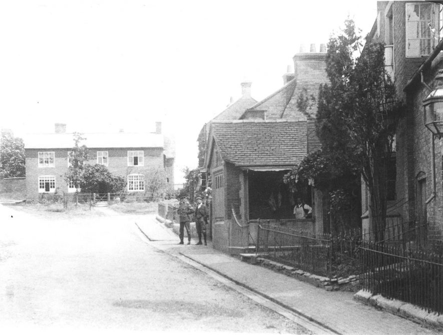 Church Hill (? now School Hill), Cubbington, showing Lambert's butchers shop on the right. Two men are standing on the pavement in front and the butcher in the shadows.  1920s |  IMAGE LOCATION: (Warwickshire County Record Office)