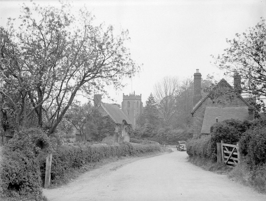 A lane in Ashow with the church tower in the background.  1956 |  IMAGE LOCATION: (Warwickshire County Record Office)