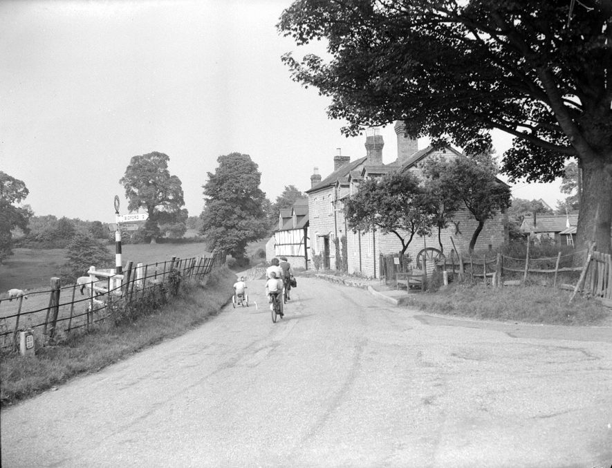 A street in Ardens Grafton. A family out cycling.  1956 |  IMAGE LOCATION: (Warwickshire County Record Office)