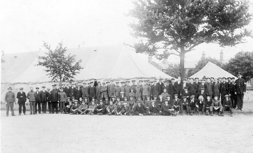 Large group of men, some in uniform, at Budbrooke Barracks in 1914. |  IMAGE LOCATION: (Warwickshire County Record Office)
