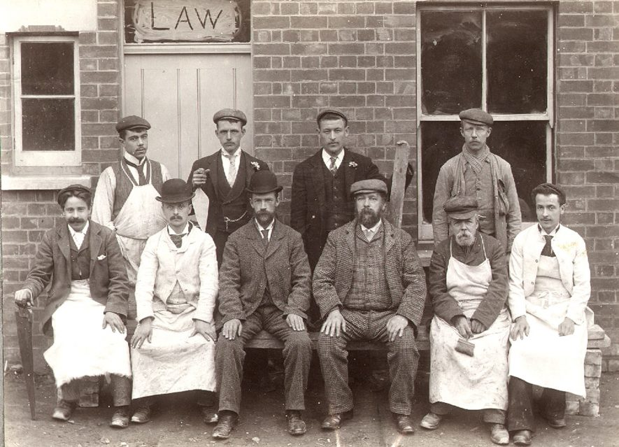 Arthur Law (in check suit) and his workmen outside a house in Dale Street, Rugby. Mr Law was in business as a painter and decorator from 1876 until 1904.  1890s |  IMAGE LOCATION: (Rugby Library) PEOPLE IN PHOTO: Law, Arthur, Law as a surname