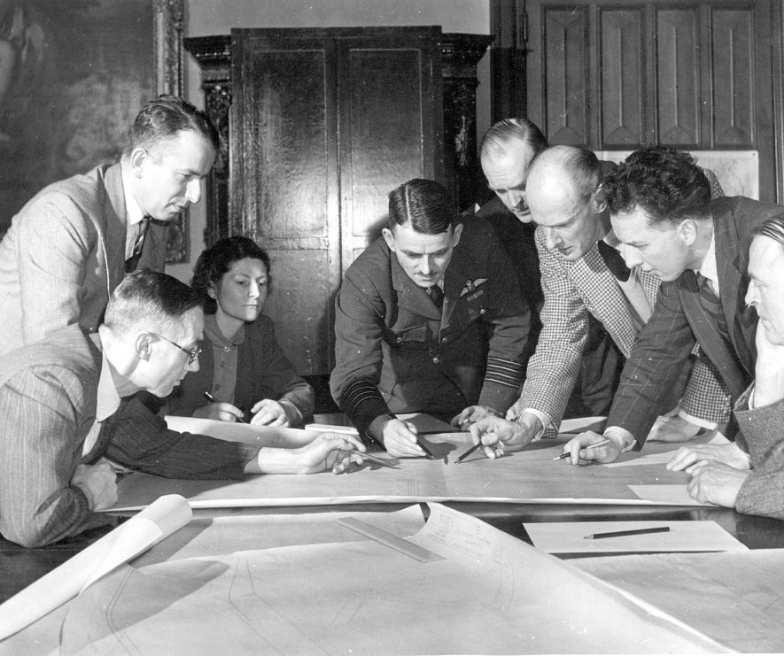 Sir Frank Whittle's research team in conference at Brownsover Hall where design work on the jet engine was carried out from 1940. left-right L J Cheshire, engineer, R Dudley Williams, director, Mary Phillips, secretary,  W E P Johnson, J C B Tinling, director, D Walker, engineer, Wing Commander George Lees, engineer.  1944 |  IMAGE LOCATION: (Rugby Library) PEOPLE IN PHOTO: Williams, R Dudley, Williams as a surname, Whittle, Frank, Whittle as a surname, Walker, D, Walker as a surname, Tinling, J C B, Tinling as a surname, Phillips, Mary, Phillips as a surname, Lees, George. Wing Commander, Lees as a surname, Johnson, W E P, Johnson as a surname, Cheshire, L J, Cheshire as a surname