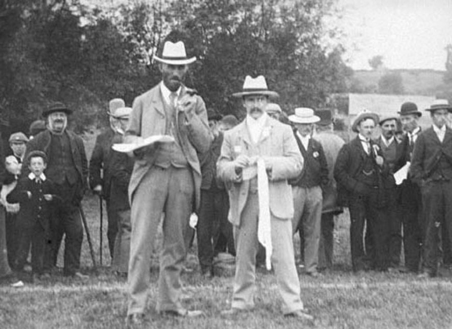 Two male officials, possibly at a sporting event, with male onlookers in Lower Brailes.  1900s |  IMAGE LOCATION: (Warwickshire Museums. Photographic Collections.)