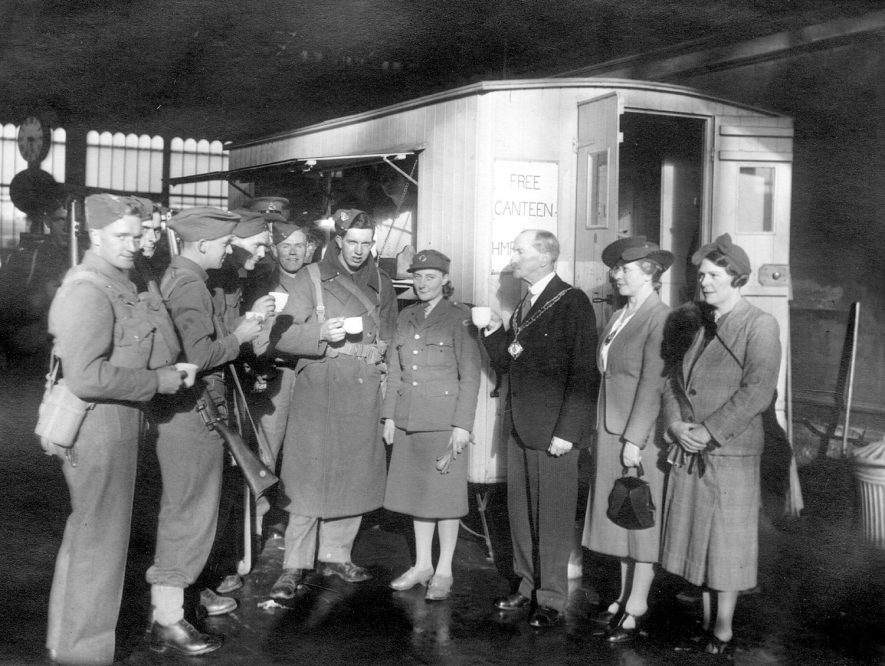 The Mayor Alderman R.H. Myers accompanied by  Miss D. Myers serves the 100,000th cup of tea from the Railway Station canteen, Rugby.  1943 |  IMAGE LOCATION: (Rugby Library) PEOPLE IN PHOTO: Myers, Alderman R H, Myers, Miss D S, Myers as a surname