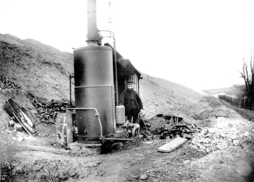 Great Central railway pumping engine and driver at Watling Street, Nuneaton, before all the drainage was completed. A very large long drain runs beside this embankment on the extreme right of the photograph.  1920s