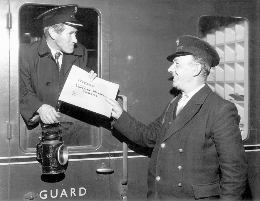 Guard John Magee, working his last week at Rugby Central Station, receiving a Leicester Mercury news packet, carried daily by a train from Rugby, from fellow guard John Best at Rugby Station.  August 10th 1966 |  IMAGE LOCATION: (Rugby Library) PEOPLE IN PHOTO: Magee, John, Magee as a surname, Best, John, Best as a surname