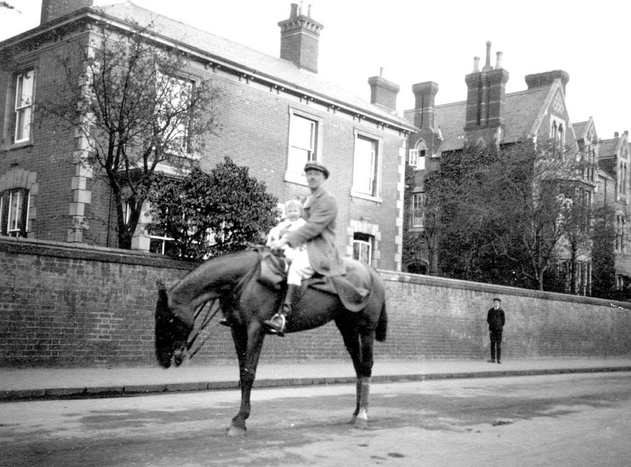 Lt. Col. Frank West sitting on his horse with one of his daughters in Horton Crescent, Rugby. Lt. Col. West married Miss Agatha Mary Dewar, elder daughter of Mr William Dewar an assistant master at Rugby School on 2nd June 1909. They lived at Bawnmore, Bilton. He was killed in action during the Battle of the Somme on 29th September 1916 leaving a widow and four daughters.  1912   See Rugby Advertisers - 5th June 1909 p.3 and 7th October 1916 p.2. |  IMAGE LOCATION: (Rugby Library) PEOPLE IN PHOTO: West, Lt Colonel F, West as a surname