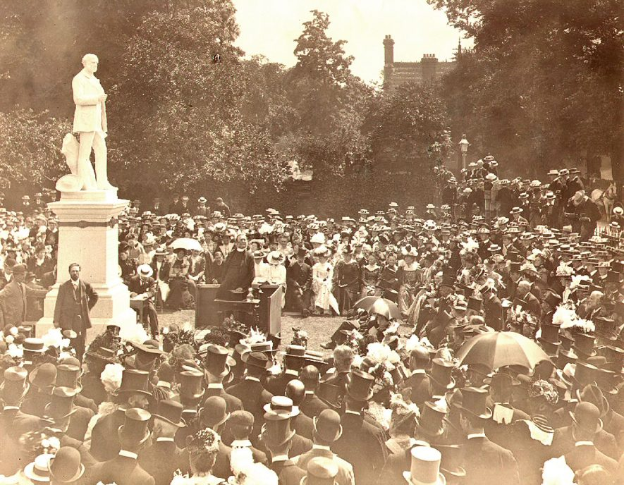 The Archbishop of Canterbury (The Most Hon. and The Rt. Rev. Frederick Temple) unveiling the Thomas Hughes Statue on June 24th 1899. This statue was erected by subscription amongst Old Rugbians and others. It is the work of Mr. T. Brock, R.A. The figure, more than life size, is of white marble and stands on a white pedestal of grey granite, the total height being about 18 feet. On the pedestal is the following inscription -