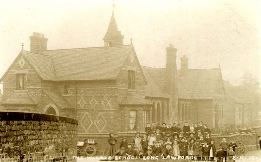 Group of children standing in front of the village school in Long Lawford.  1900s |  IMAGE LOCATION: (Rugby Library)
