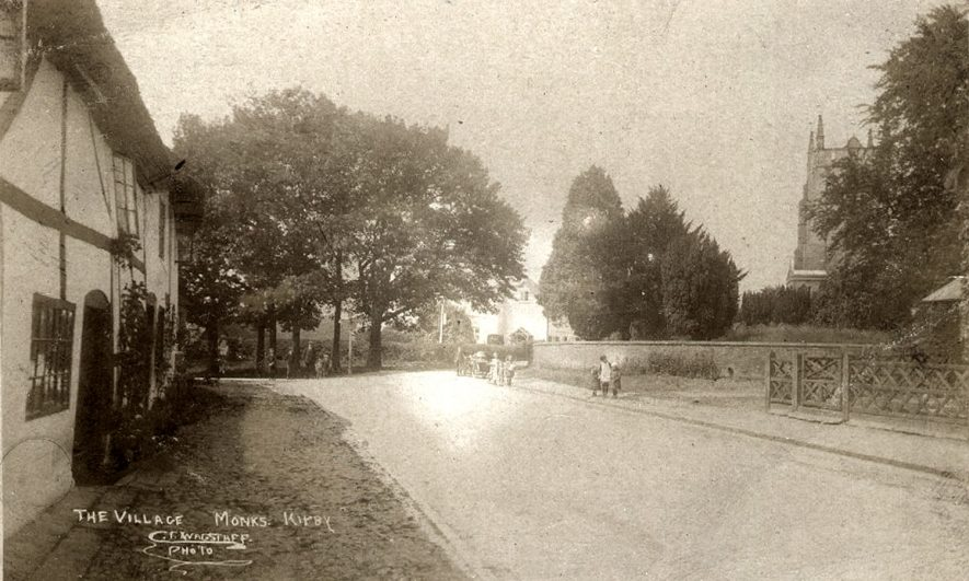 A village street in Monks Kirby, with the church partly hidden by trees to the right. Children and adults are standing in the road. A motorcycle and sidecar are also pictured.  1910s |  IMAGE LOCATION: (Rugby Library)