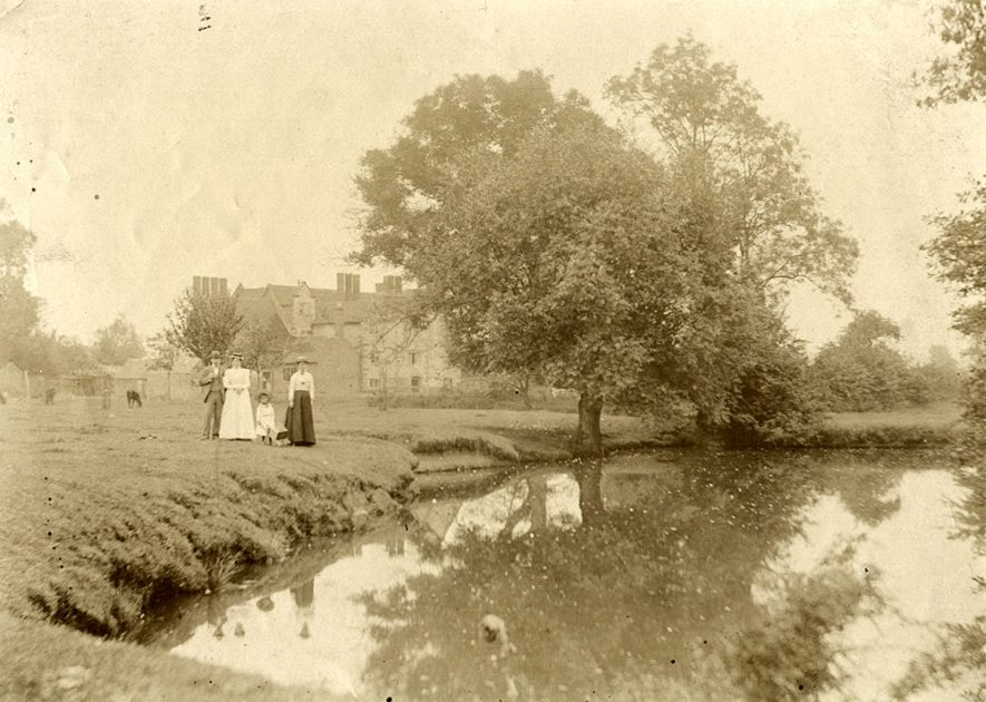 Mr and Mrs A.E. Treen and Mrs Wilson standing beside the River Avon and in front of The Manor House at Brandon.  1908