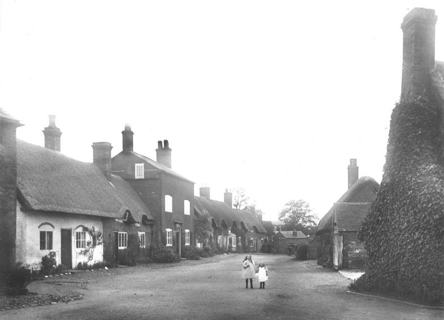 School Street in Dunchurch in 1899. The two cottages on the left were demolished. The site is now occupied by Dunchurch Library.[The cottage in the middle was turned into a council yard with washhouses before it became the library] |  IMAGE LOCATION: (Rugby Library)
