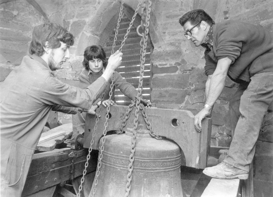 St Peter's Church bells being taken down to be repaired and restored by Taylors of Loughborough, Dunchurch.  Bellhangers from G J Batchelor's, Rugby: left-right John Hughes, Mark Winward, Austin Gooch.  1981 |  IMAGE LOCATION: (Rugby Library) PEOPLE IN PHOTO: Winward, Mark, Winward as a surname, Hughes, John, Hughes as a surname, Gooche, Austin, Gooche as a surname