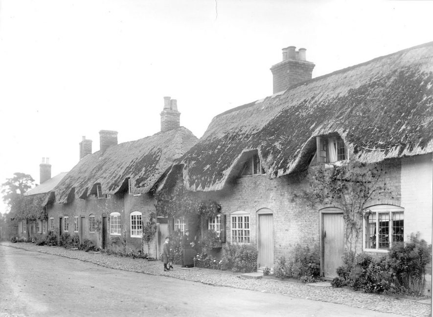 Row of thatched cottages with a woman and boy by a doorway, Dunchurch.  1899 |  IMAGE LOCATION: (Rugby Library)