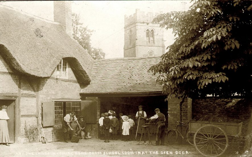 Blacksmith's shop, Dunchurch.  Children from school look in at open door.  Blacksmiths at work, woman in doorway, two-wheeled cart and bicycle under chestnut tree.  Church tower in background.  1906 |  IMAGE LOCATION: (Rugby Library)