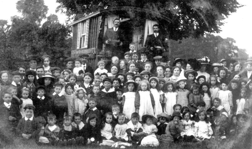 Group of children in front of a caravan at Long Lawford during a visit of missionaries. The two men standing at the back are - on the left - G. Aldridge (ex miner) and on the right - Mr Garrett (local baker).  1920 |  IMAGE LOCATION: (Rugby Library) PEOPLE IN PHOTO: Garrett, Mr, Garrett as a surname, Aldridge, G, Aldridge as a surname