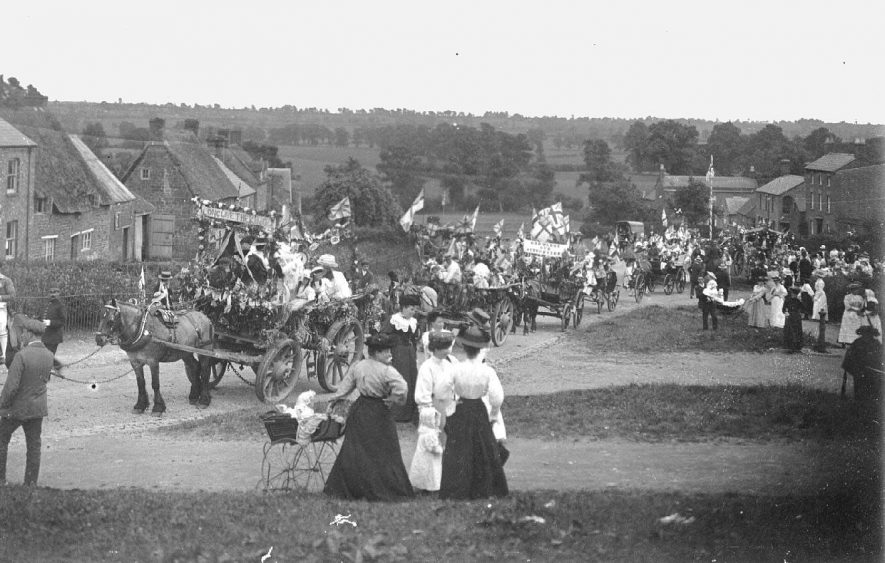 Coronation celebrations proceeding through the High Street; parade with decorated horse drawn carts and mock coronation coach filled with children, adults, flags and banners. Small crowd watching.  1911 |  IMAGE LOCATION: (Warwickshire County Record Office)